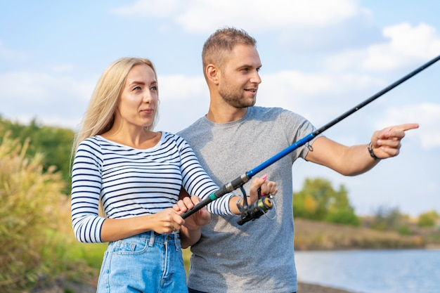 Happy young couple fishing by lakeside