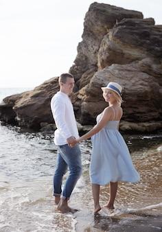 海の近くでポーズをとって幸せな若いカップルの将来の両親