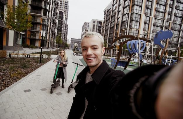 幸せな若いカップルは、eスクーターに乗って楽しい時間を過ごします。高速旅行のコンセプト。ロマンチックなデート。若い金髪の男はカメラを持って、魅力的なガールフレンドと一緒に自分撮りをします。
