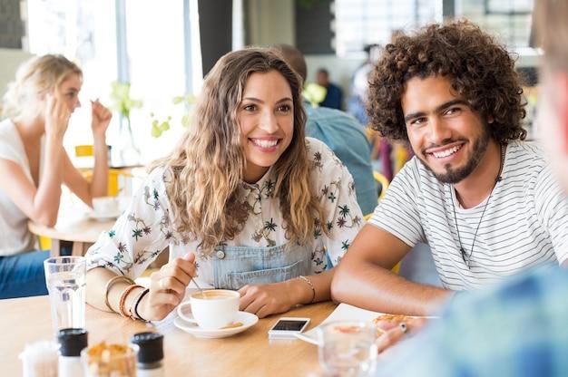 友人とカフェテリアで朝食をとって幸せな若いカップル