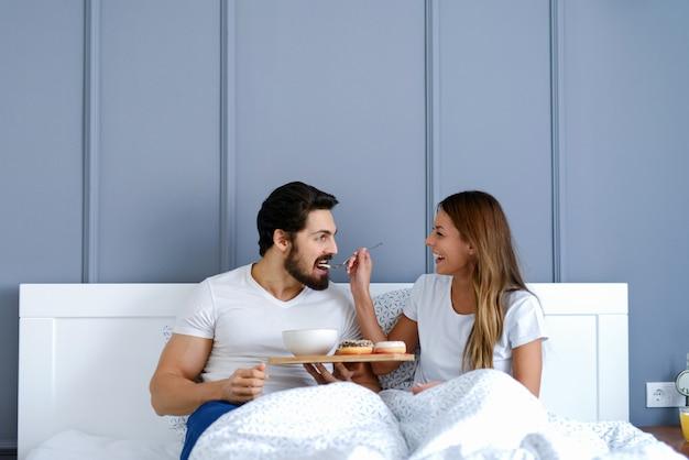 彼らのベッドで朝食を持っている幸せな若いカップル。美しい少女は彼女のハンサムなボーイフレンドを供給しています。