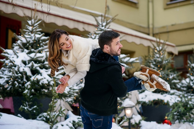 Happy young couple having fun on winter cityscape  of christmas tree with lights. winter holidays, christmas and new year .