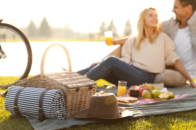 Happy young couple having picnic near lake, focus on wicker basket with blanket and hat