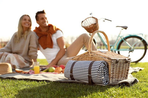 Happy young couple having picnic outdoors, focus on wicker basket