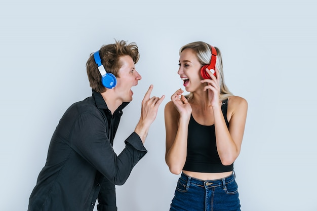 Happy young couple in headphones listening music