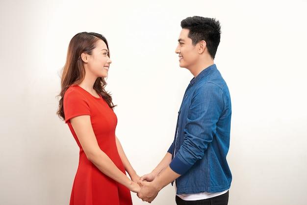 手をつないで、白い背景で笑って幸せな若いカップル