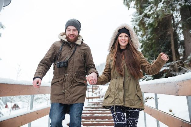 冬に手をつないで階段を駆け下りる幸せな若いカップル