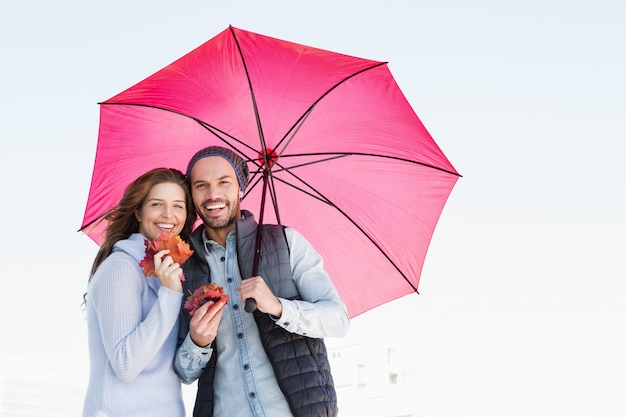 Happy young couple holding umbrella and maple leaves outdoors