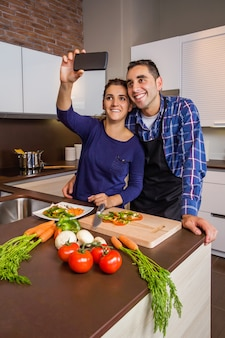 Happy young couple in a home kitchen taking a selfie with a smarphone while preparing healthy food. modern family lifestyle concept.