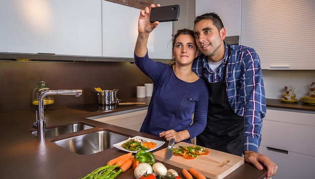 Happy young couple in a home kitchen taking a selfie with a smarphone while preparing healthy food