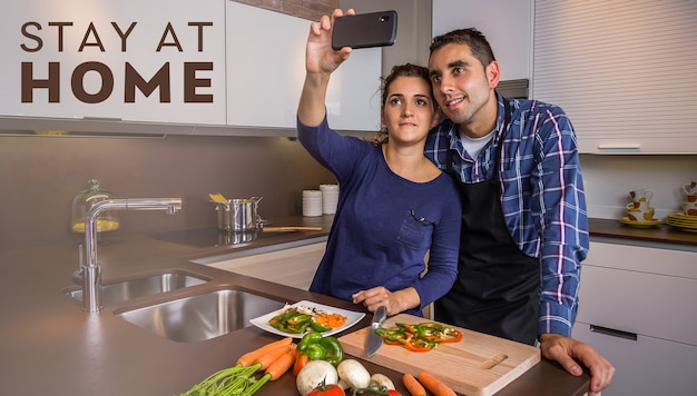 Happy young couple in a home kitchen taking a selfie with a smartphone while preparing healthy food during virus confinement