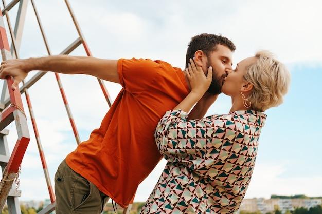 Счастливая молодая пара обниматься и смеяться на открытом воздухе на лестнице