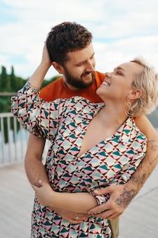 幸せな若いカップルが屋外で抱き締めて笑っています。