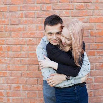 Happy young couple hugging and smiling.