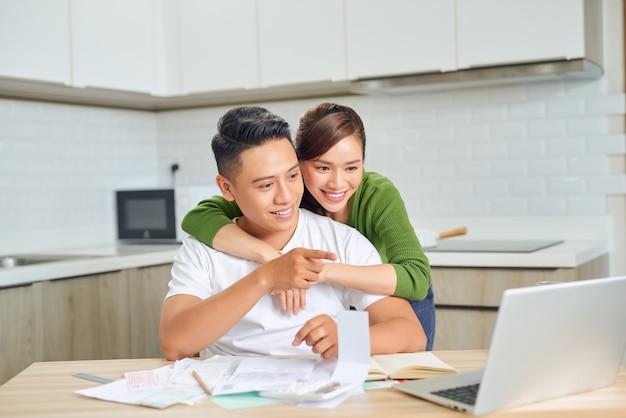 アプリでオンラインで画面の支払い請求書を見てラップトップコンピューターを使用して幸せな若いカップルの夫と妻は住宅ローンの投資支払いを計算します