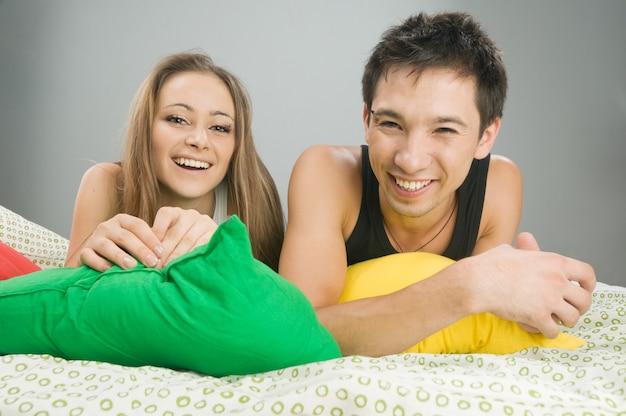 カラフルな枕とベッドで幸せな若いカップル