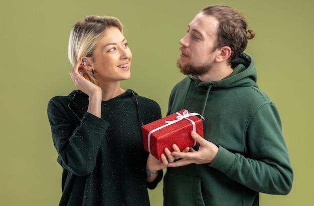 녹색 벽 위에 서있는 발렌타인 데이를 축하 그의 사랑스러운 웃는 여자 친구를위한 선물 캐주얼 옷 남자에서 행복 한 젊은 커플