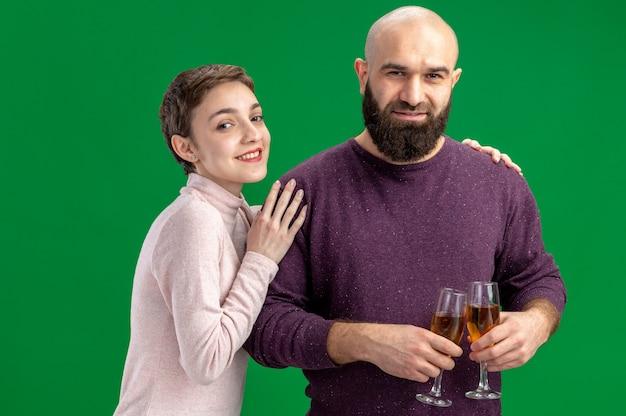 짧은 머리와 샴페인 안경 수염 남자 캐주얼 옷 여자 행복 젊은 부부 함께 녹색 벽 위에 서있는 발렌타인 데이를 축하 사랑에 행복