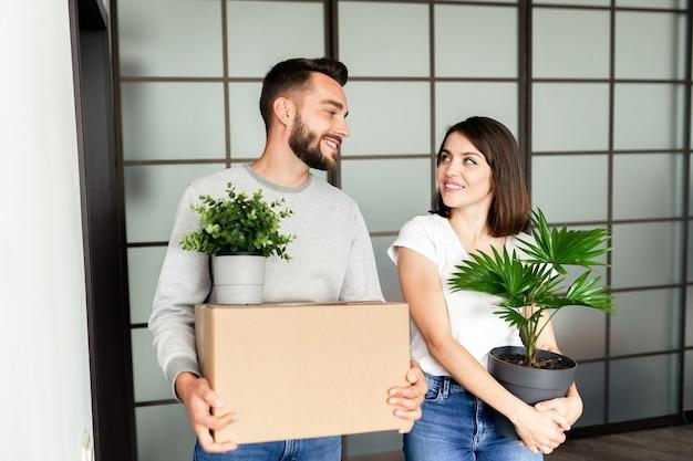 Счастливая молодая пара в повседневных нарядах взволнована движением, стоя в современной комнате и держа вещи, глядя друг на друга