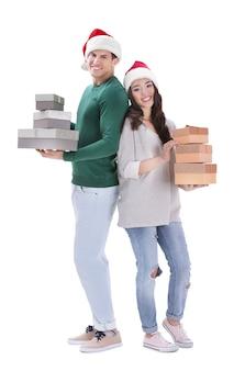ギフトボックスを保持しているクリスマス帽子の幸せな若いカップル、