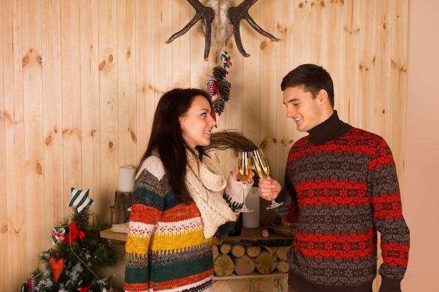 クリスマスのお祝いのために木造住宅の中でシャンパンフルートグラスを投げる色付きの冬の衣装で幸せな若いカップル。