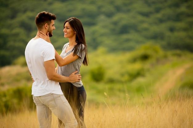 Счастливая молодая влюбленная пара на траве поля в летний день