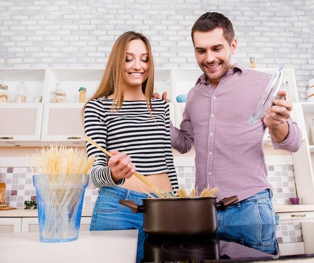 キッチンでパスタを沸騰させる愛の幸せな若いカップル