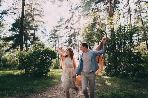 愛の幸せな若いカップルは、公園を歩いている間楽しんでいます。