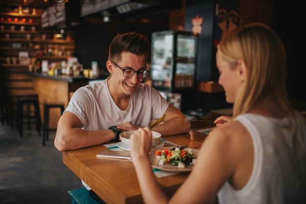 Счастливая молодая влюбленная пара, приятное свидание в баре или ресторане. они рассказывают истории о себе, пьют чай или кофе и едят салат и суп.