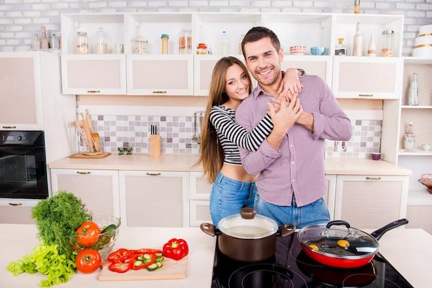 Счастливая молодая влюбленная пара обнимается и готовит завтрак на кухне