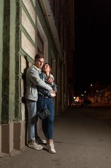 夜の街で恋に幸せな若いカップル。男は彼のガールフレンド、バックグラウンドで夜の街を抱擁します。路上でロマンチックなデート