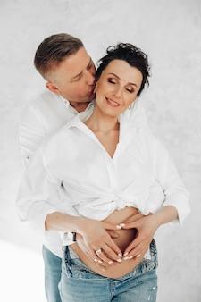 Счастливая молодая влюбленная пара в одной одежде ждет своего первого ребенка