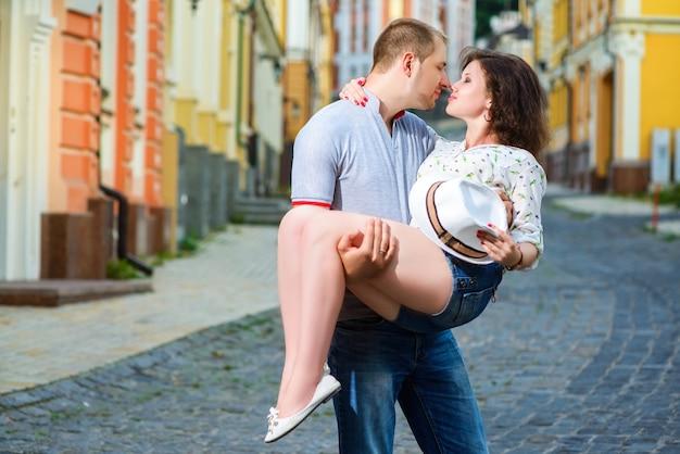 街でポーズをとって恋に幸せな若いカップル