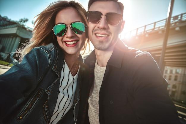 愛の幸せな若いカップルは自分撮りの肖像画を撮ります