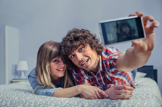 Счастливая молодая влюбленная пара, делающая селфи со смартфоном, лежащим над кроватью. свободное время дома концепции.