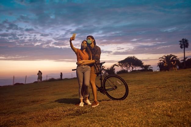 아름다운 일몰 공원에서 함께 셀카를 복용 사랑에 행복 한 젊은 커플