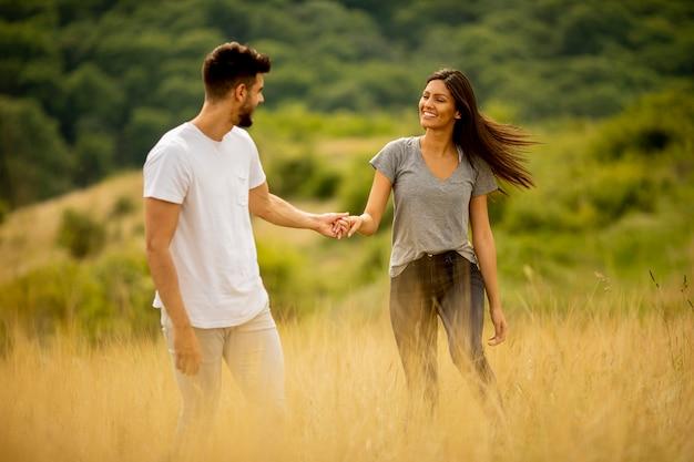 Счастливая молодая влюбленная пара гуляет по траве в летний день