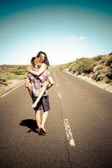 長いまっすぐな道を一緒に歩いて恋に幸せな若いカップル Premium写真