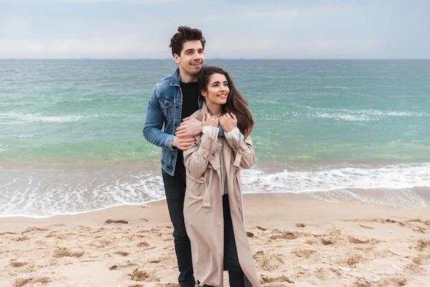 海辺で一緒に時間を過ごし、抱き締めて秋のコートを着て恋に幸せな若いカップル
