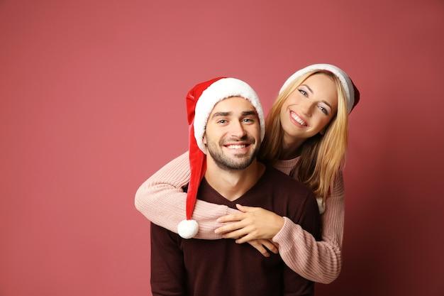 색상 배경에 산타 모자에 행복 한 젊은 커플. 크리스마스 컨셉