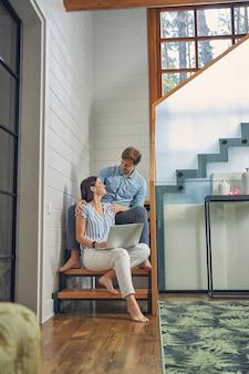거실에서 행복 한 젊은 커플 그들의 집은 나무 계단에 앉아있는 동안 서로를 찾고