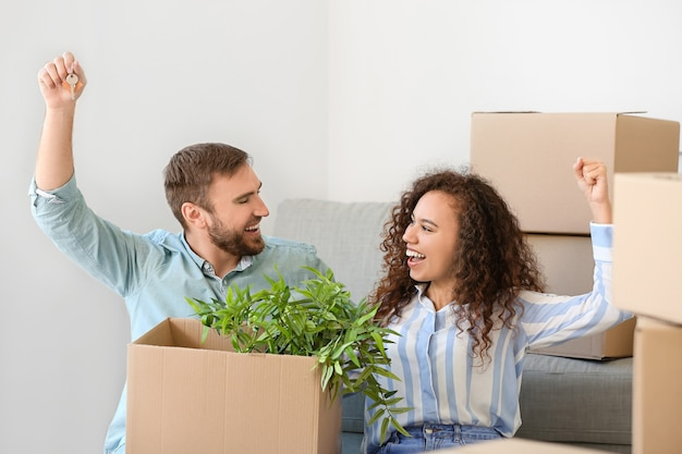 Счастливая молодая пара в своей новой квартире в день переезда