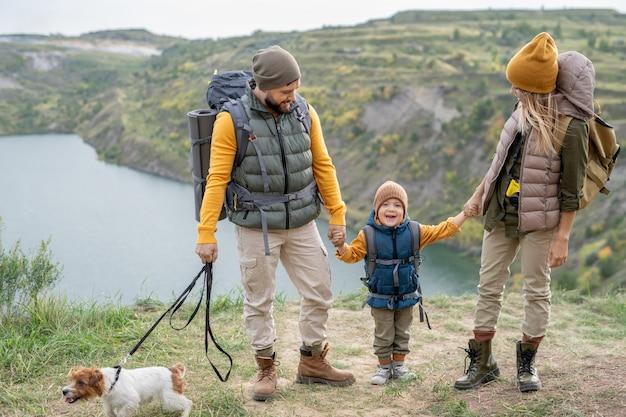 旅行中に川沿いや山々に対して地面に立っている間彼らのかわいい幼い息子を見ている暖かいカジュアルウェアで幸せな若いカップル