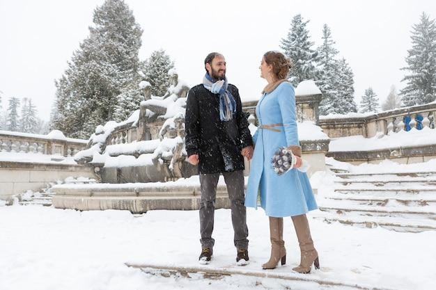 ウィンターパークで幸せな若いカップル。城の屋外の家族。