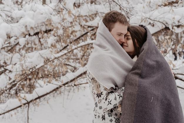 Счастливая молодая пара в зимнем парке, весело. семья на открытом воздухе. любить.
