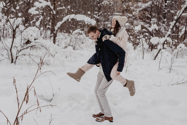 楽しんでいるウィンターパークの幸せな若いカップル。家族の屋外。愛。