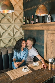 幸せな若いカップルはコーヒーを飲み、カフェに座っている笑顔