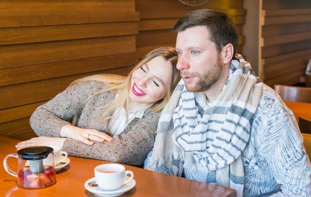 행복 한 젊은 커플은 커피를 마시고 카페에 앉아있는 동안 웃 고.
