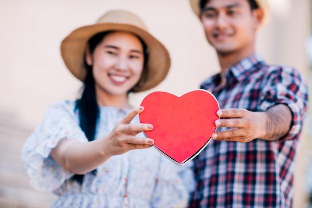 幸せな若いカップルは赤い紙の心を持っています。
