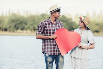 Happy young couple is holding red paper hearts